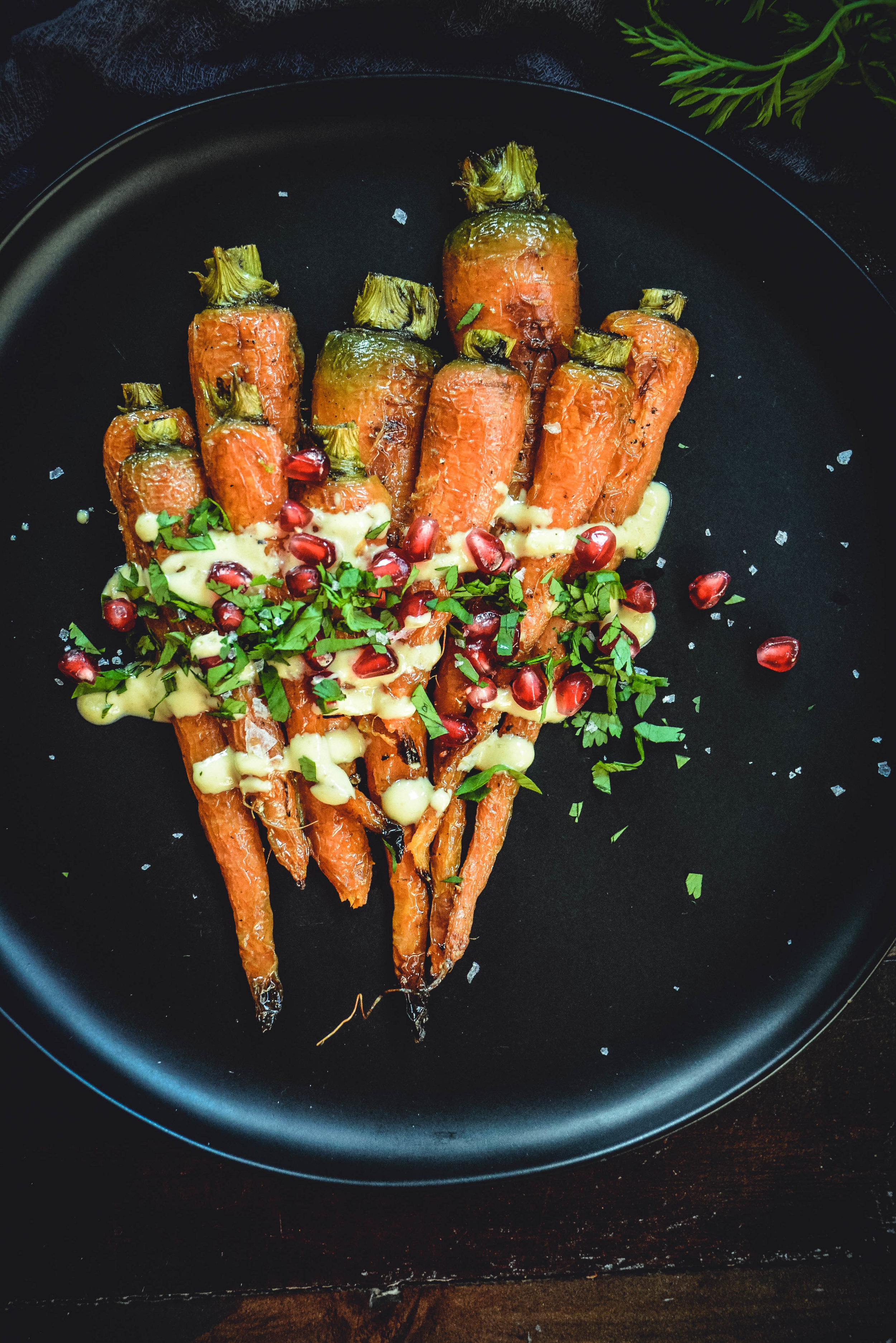 Take roasted carrots to a new level with this flavorful, creamy tahini sauce, topped with finely chopped cilantro and pomegranate seeds. They're a feast for the eyes and the taste buds! Bonus, they're vegan, paleo and whole 30 approved! #calmeats #paleo #whole30 #vegansides #paleosides #vegansides #whole30sides #roastedcarrots #carrots #realfood #glutenfreesides #dairyfreesides #tahini #pomegranate