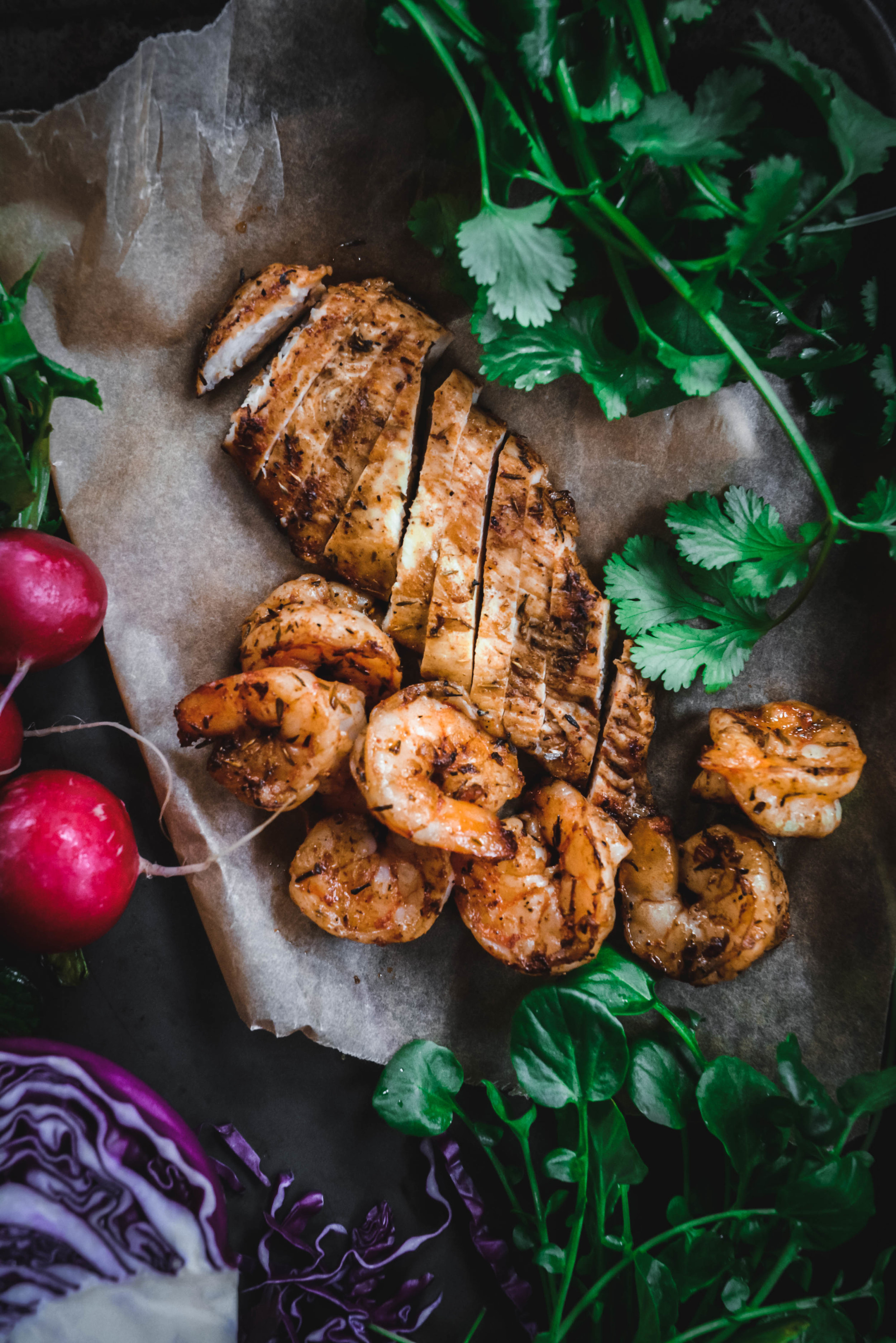 Jerk chicken and shrimp on tray with greens