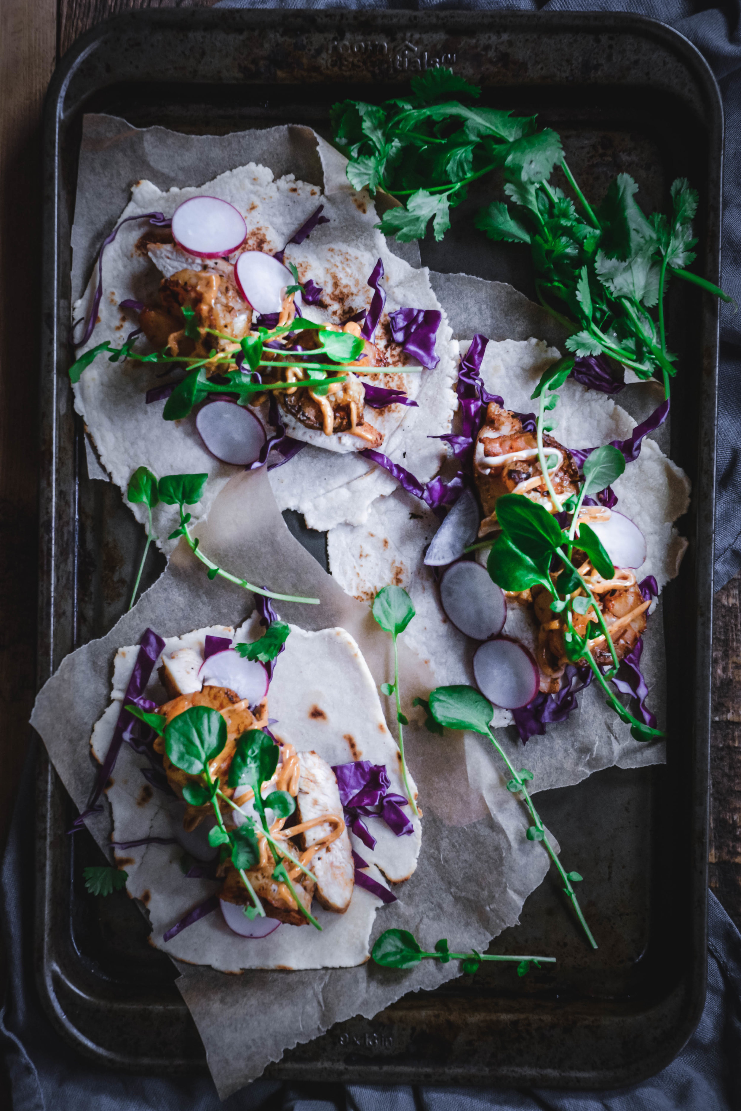 jerck chicken and shrimp tacos on tray with greens and purple cabbage