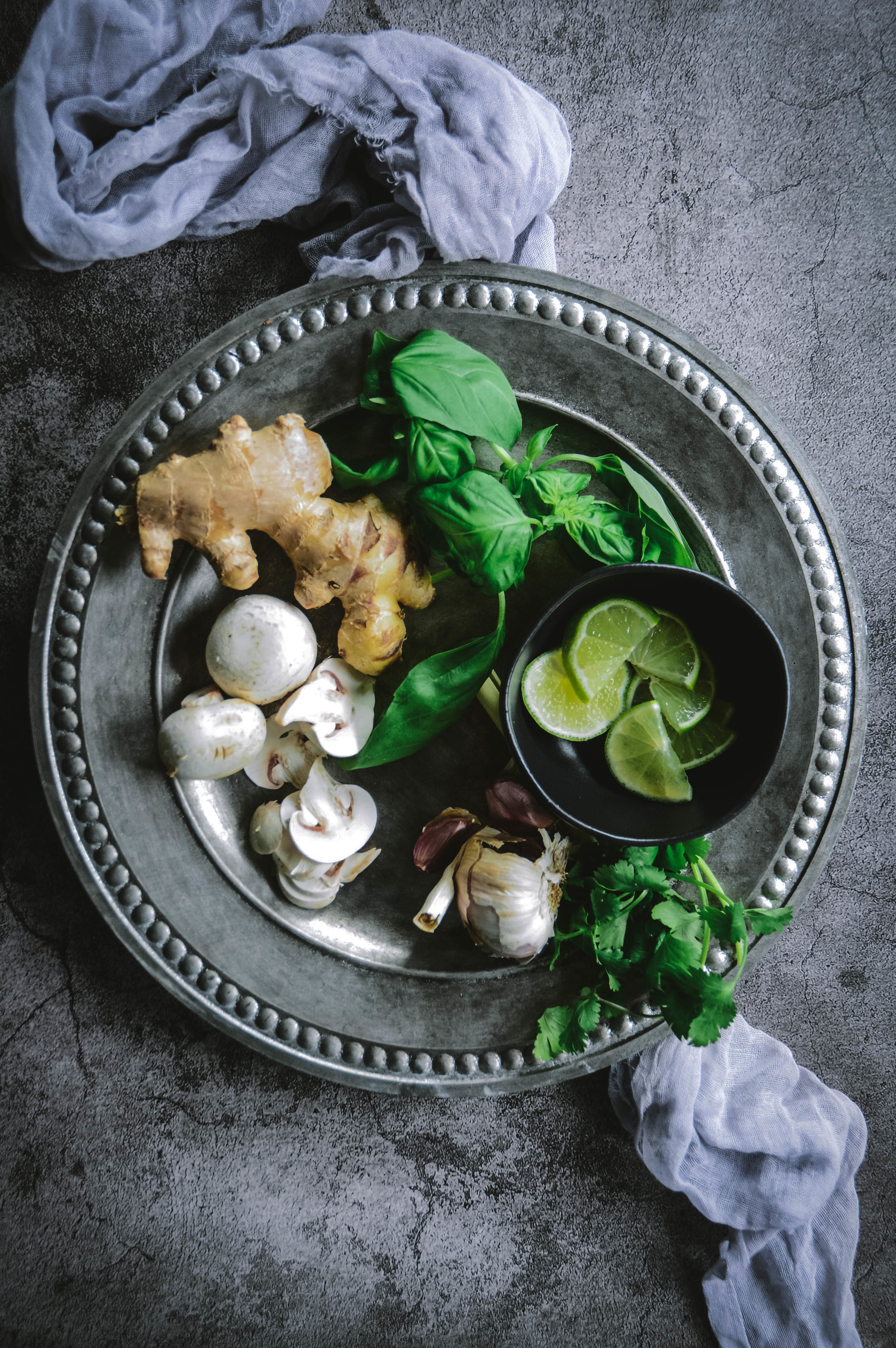 garlic ginger, mushrooms, lime and basil on plate with napkin
