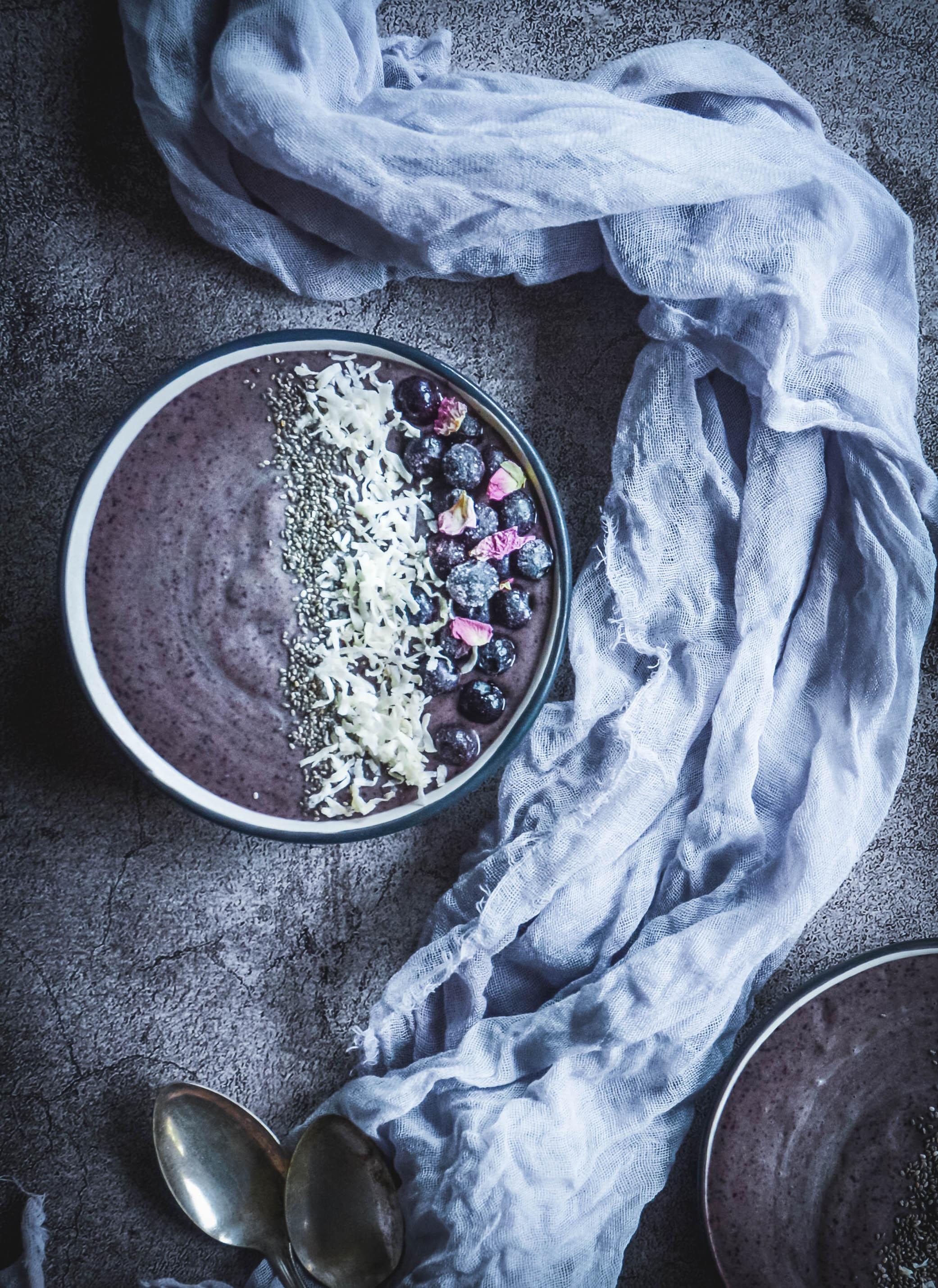 Smoothie bowl with frozen blueberries, napkin, spoon
