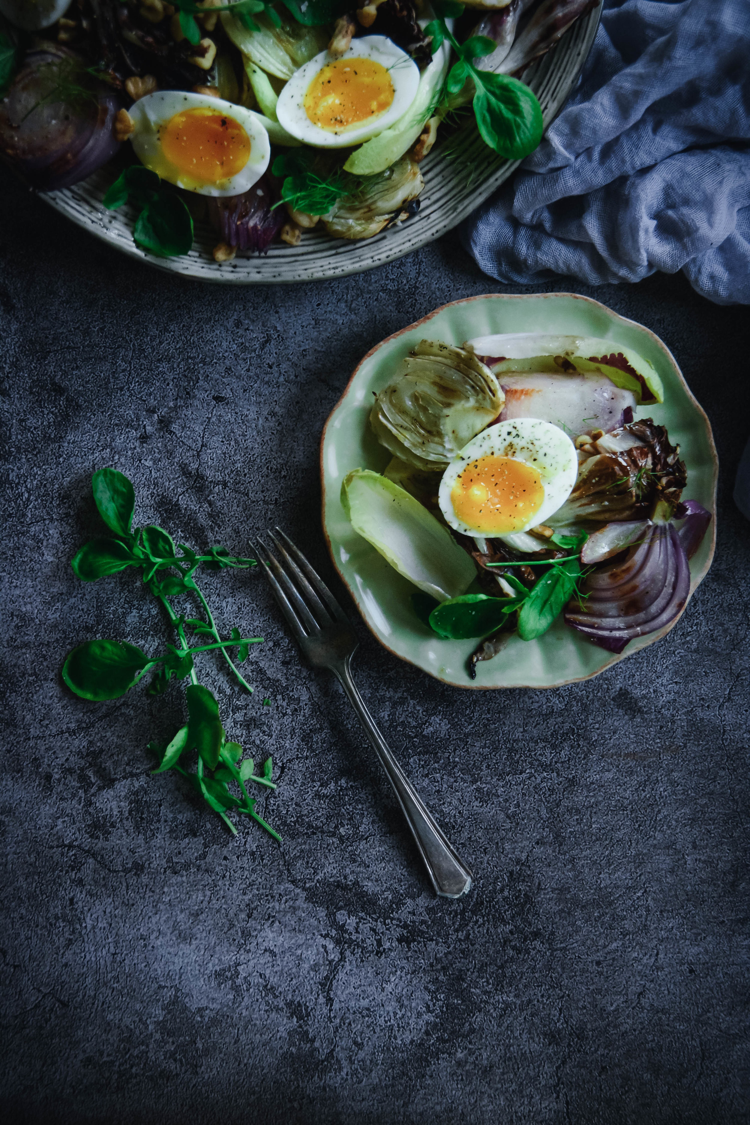 Radicchio salad on plates with greens, napkin and soft boiled eggs