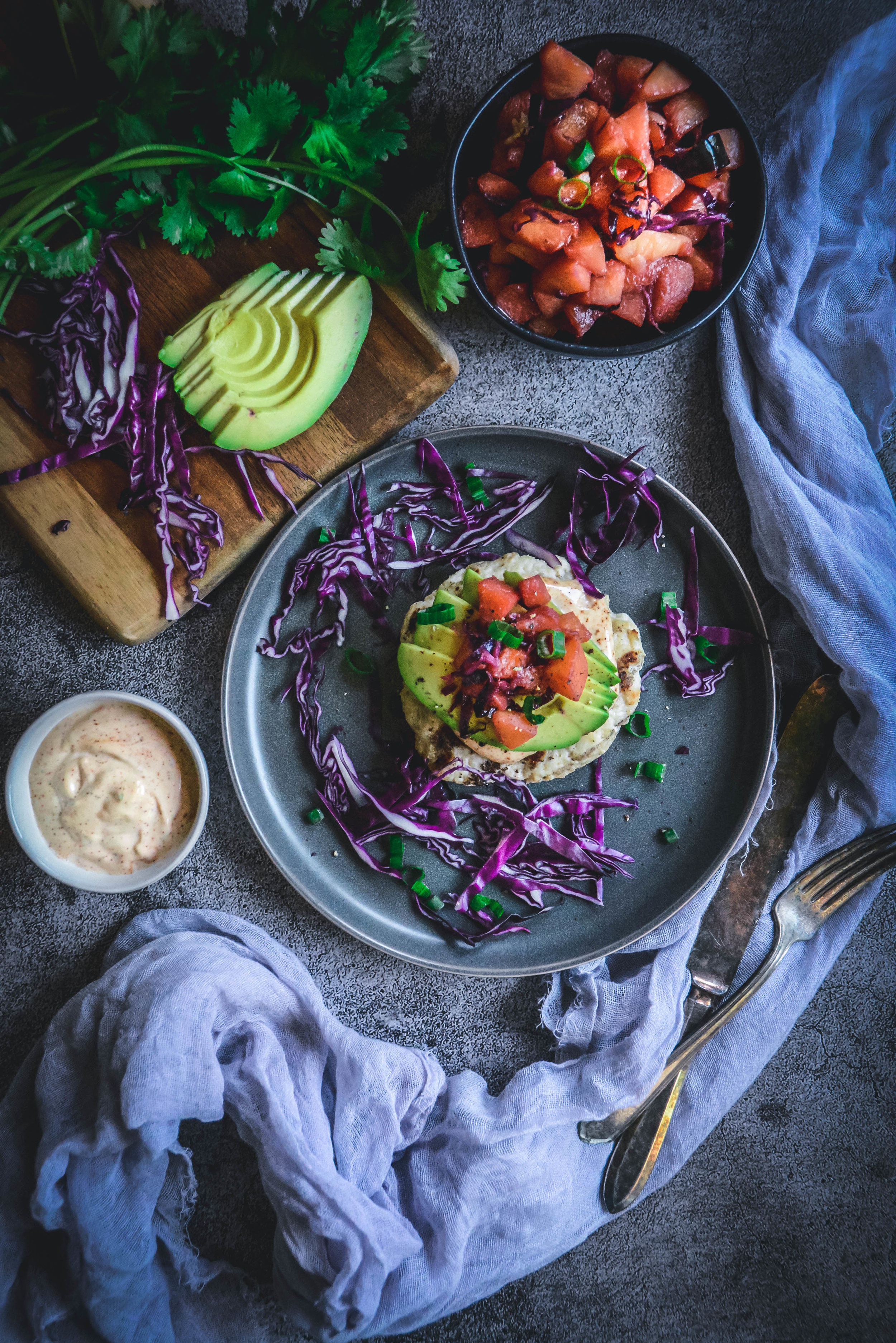 Turkey burgers with peach chutney and avocado, spicy mayo, a bowl of peach chutney, avocado slices, red cabbage, cutting board, napkin and fork and knife
