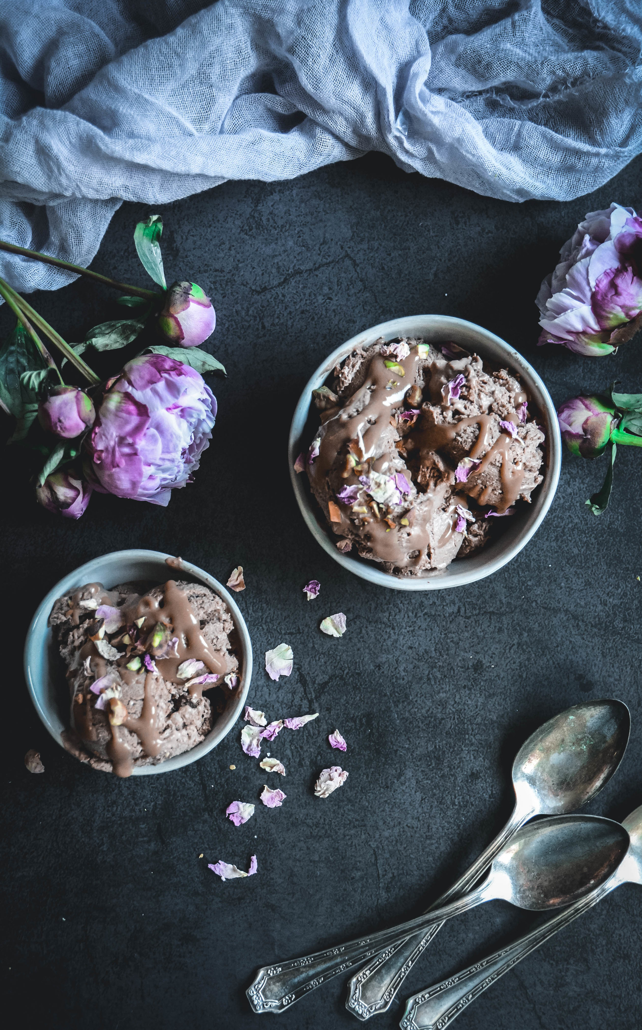 chocolate ice cream in bowl with napkin, spoons and peony's