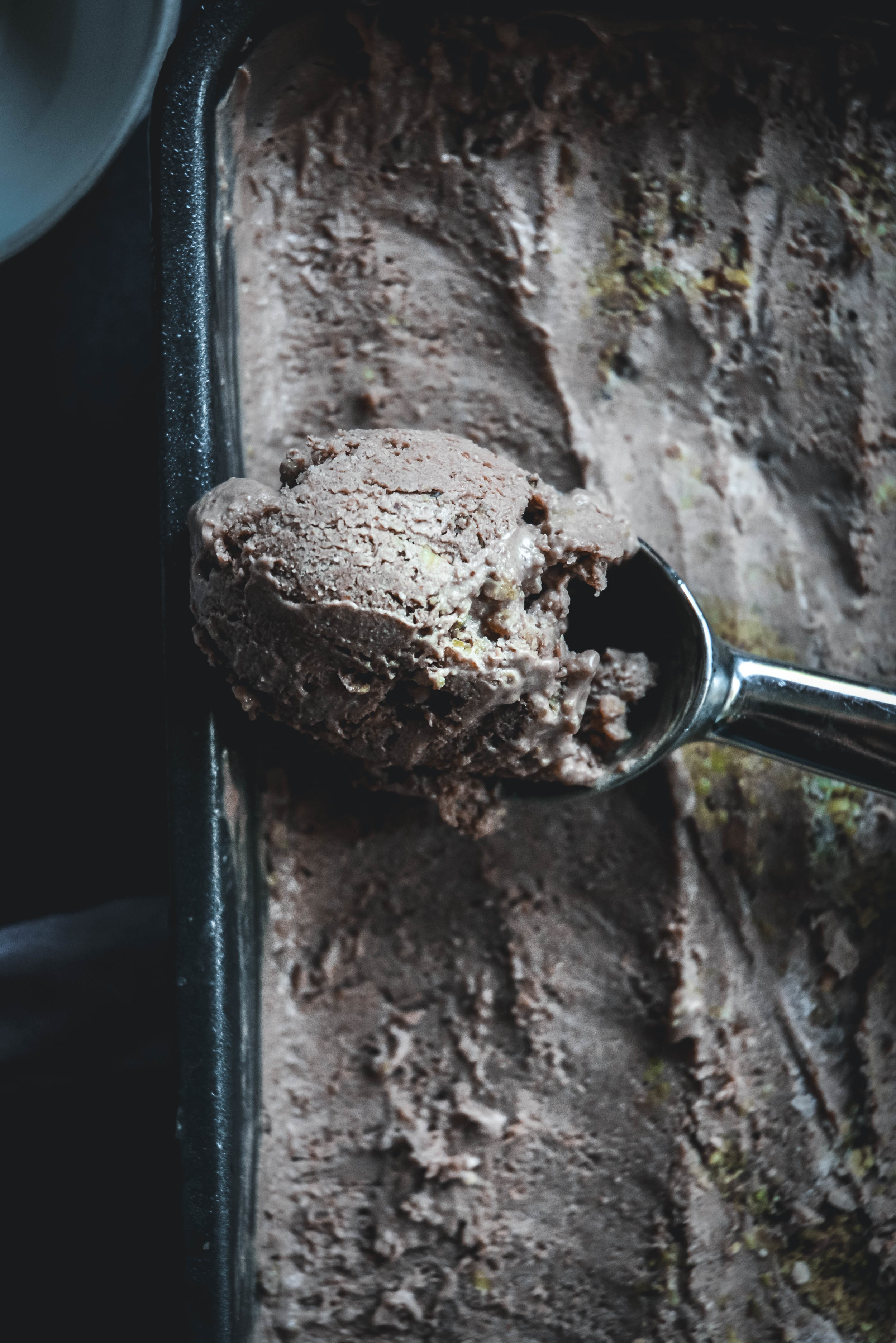 chocolate ice cream in loaf pan with scoop