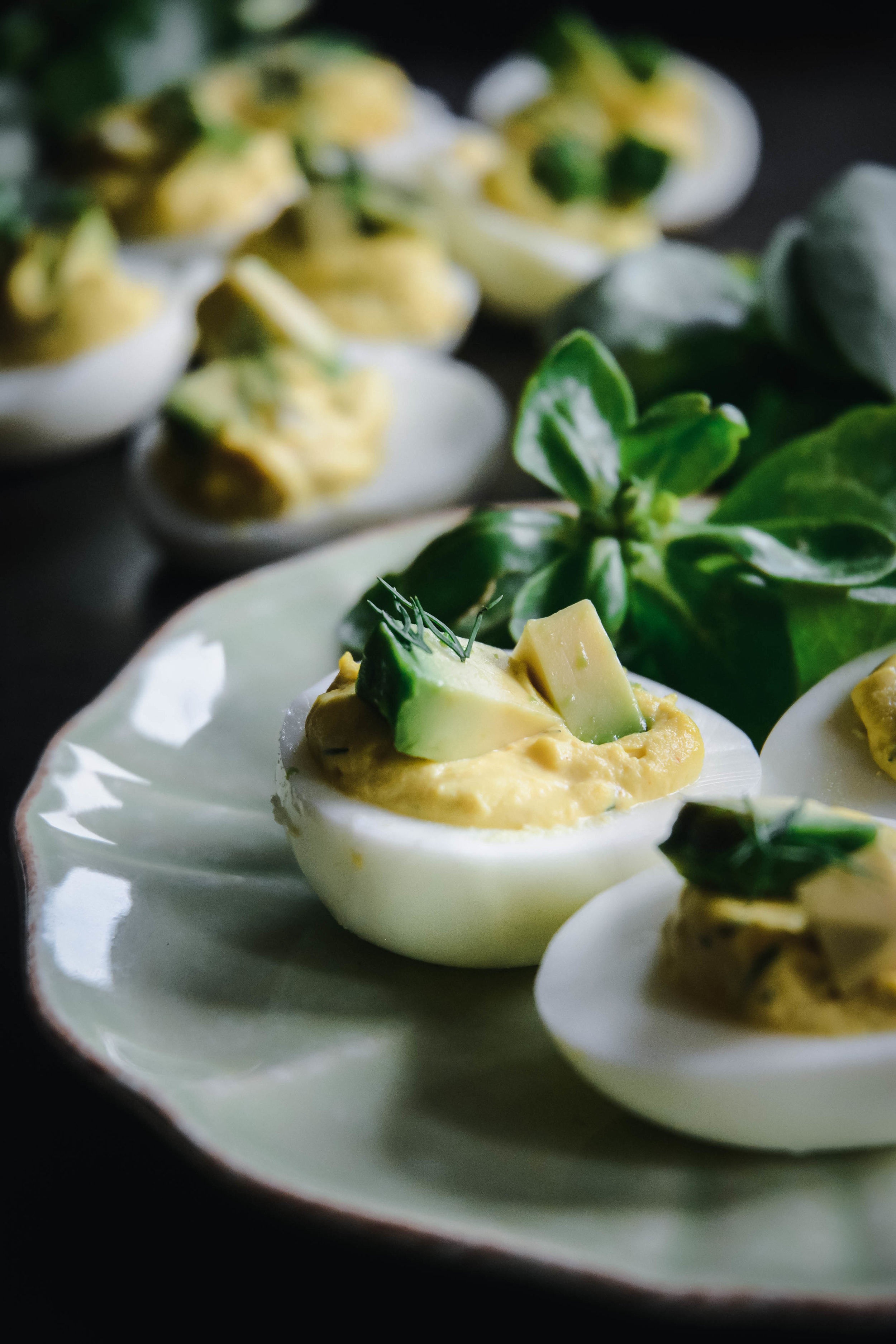 Deviled eggs on plate with avocado