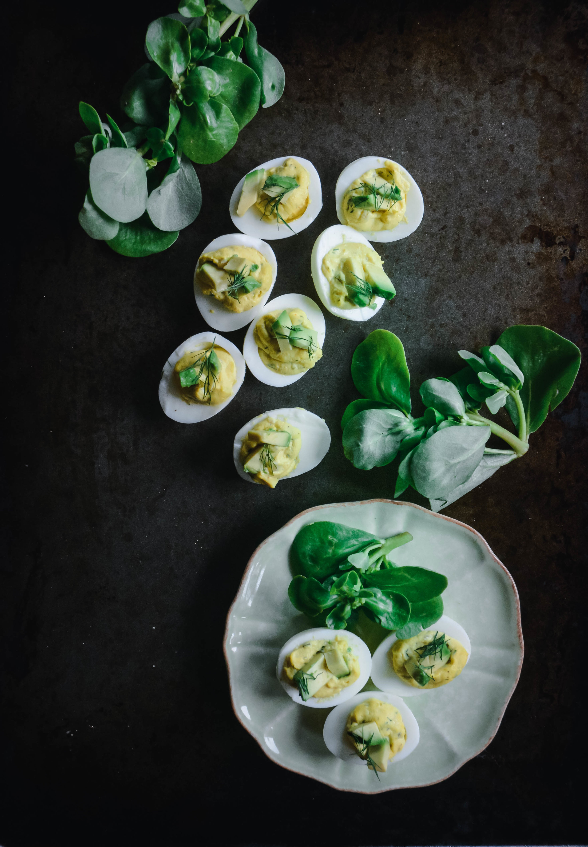deviled eggs on table and plate with greens