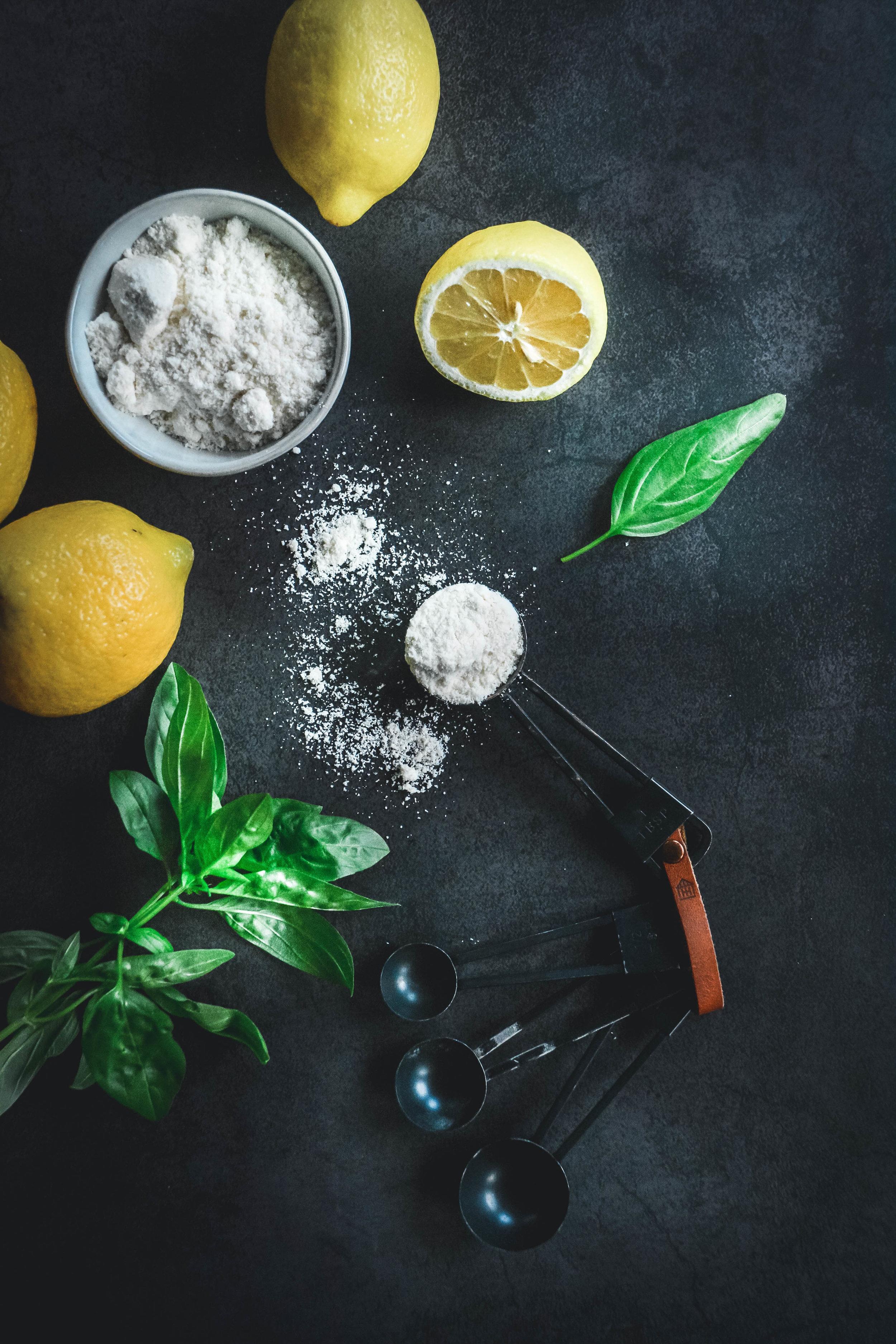 Lemons, coconut flour, measuring spoons, greens