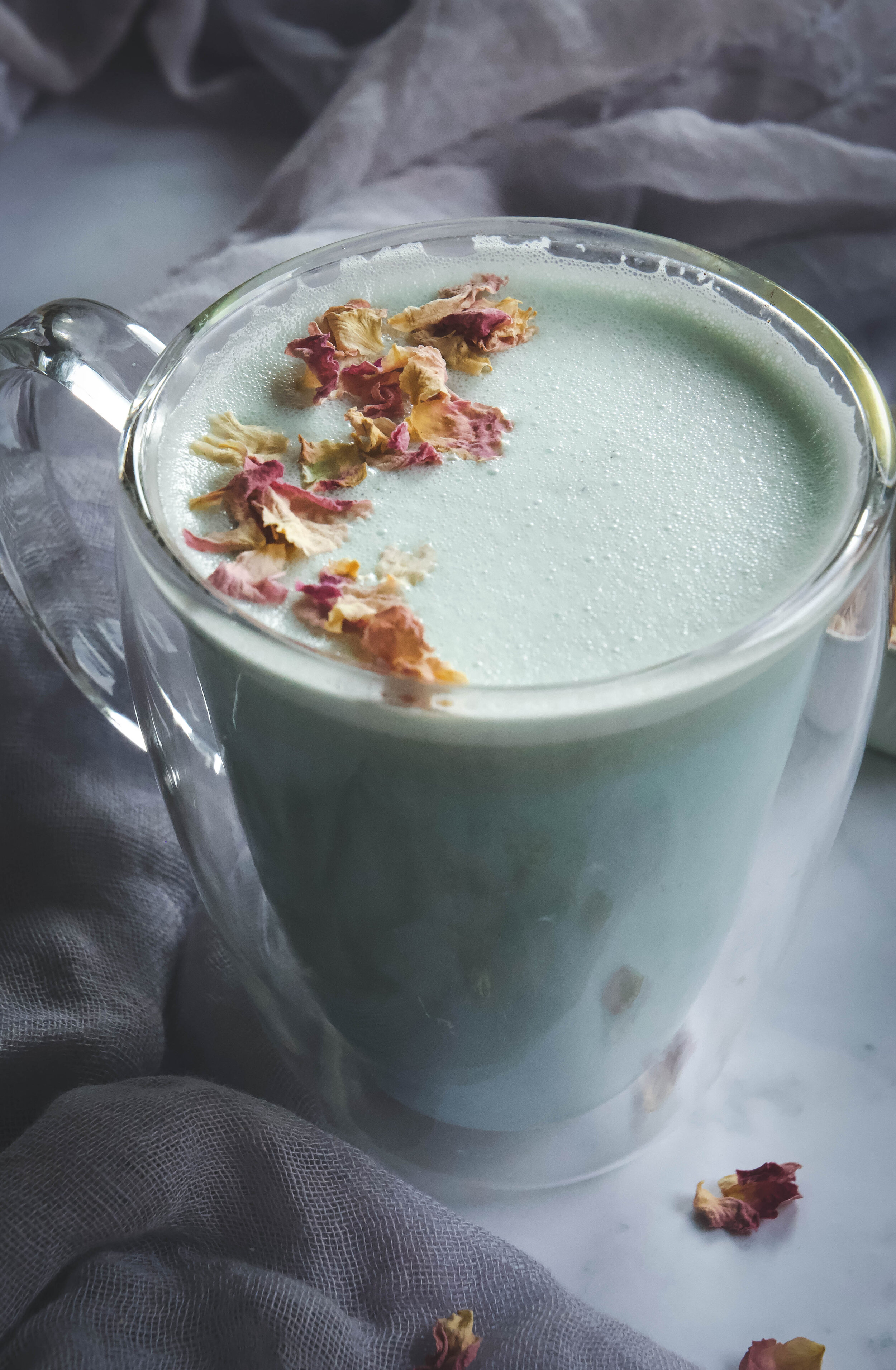 Cardamom blue moon milk in cup with rose petals