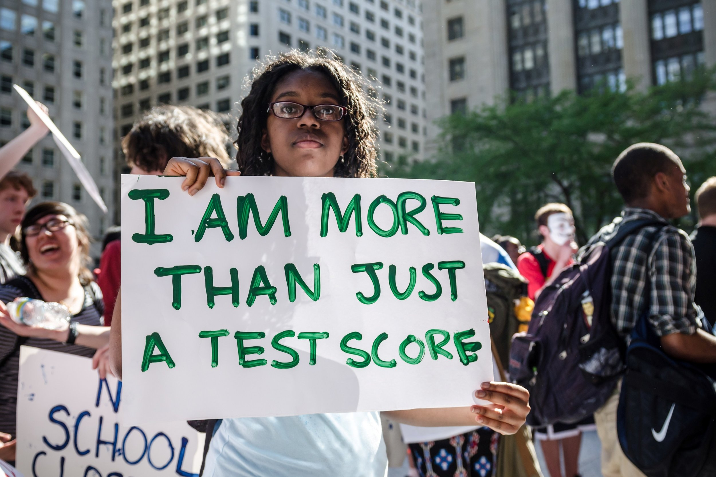 "Providence student protests for Student Bill of Rights with sign ""I am more than just a test score""."