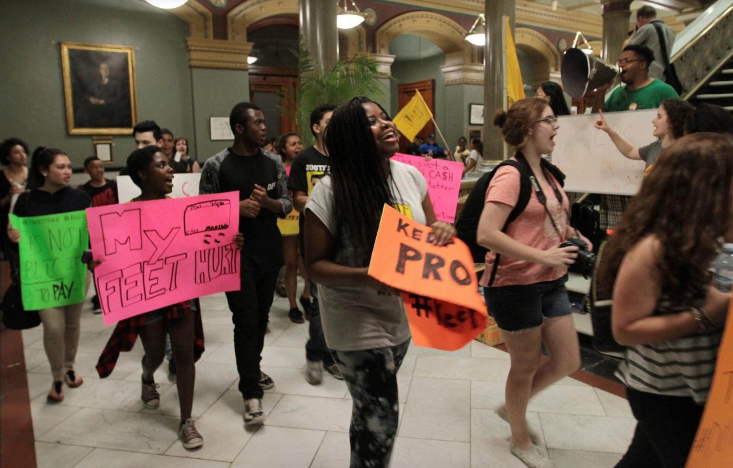 "PSU Students march through Providence City Hall for the ""Walk in Our Shoes"" campaign, carrying multi-color signs."