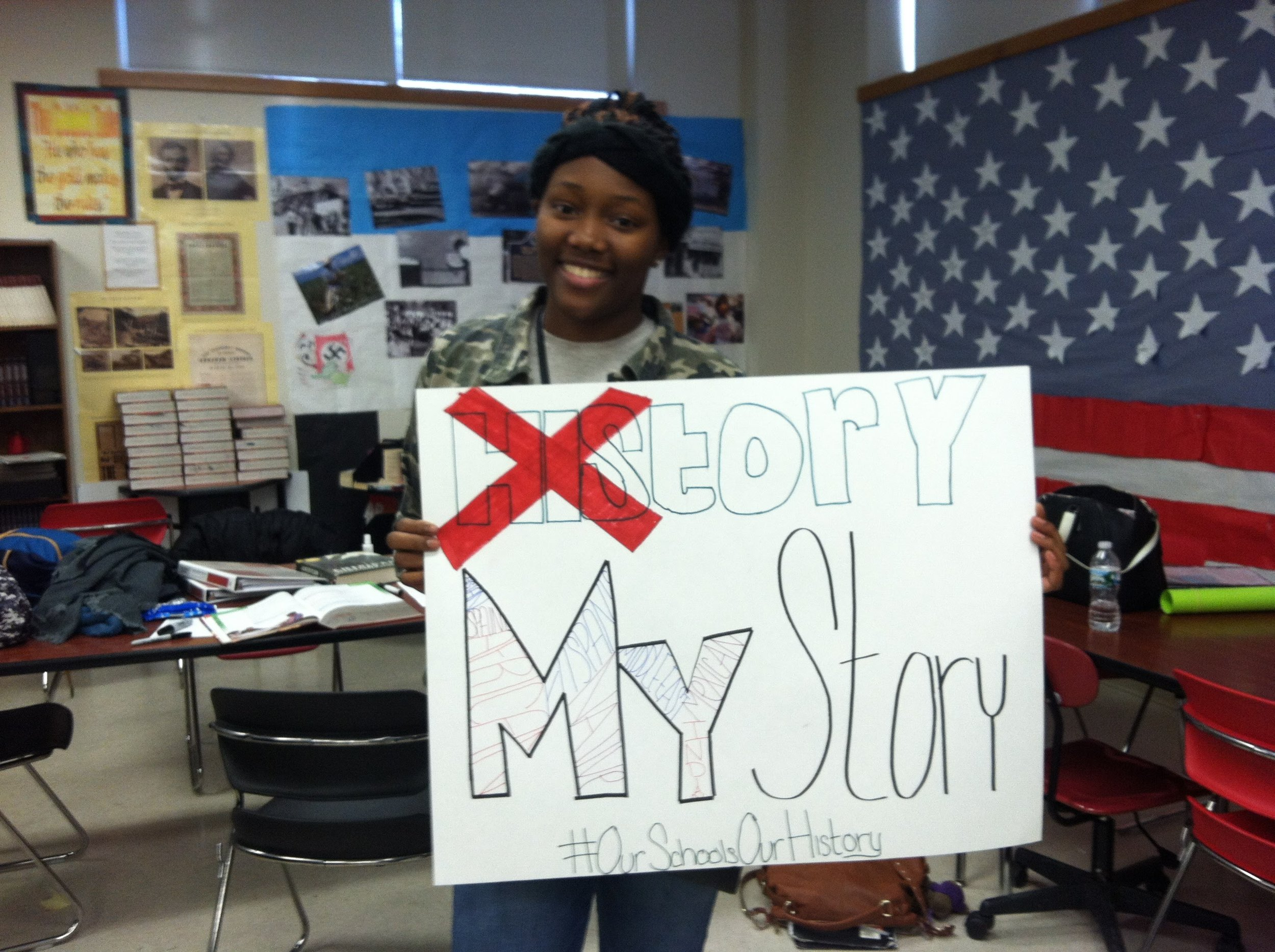 "A young female black high school student holds a sign with the word 'his' crossed out in 'history'. Beneath reads, ""My Story #OurSchoolOurHistory""."
