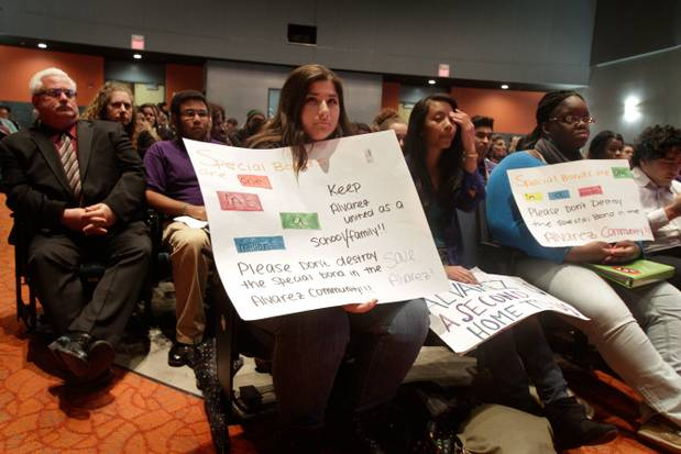 "Students and adults sit in an auditorium with signs demanding the city ""Keep Alvarez [High School] united as a school/family""."