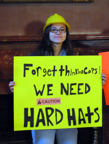 "A young female student wears a yellow construction cap holding a sign which reads, ""Forget thinking caps! WE NEED HARD HATS"""