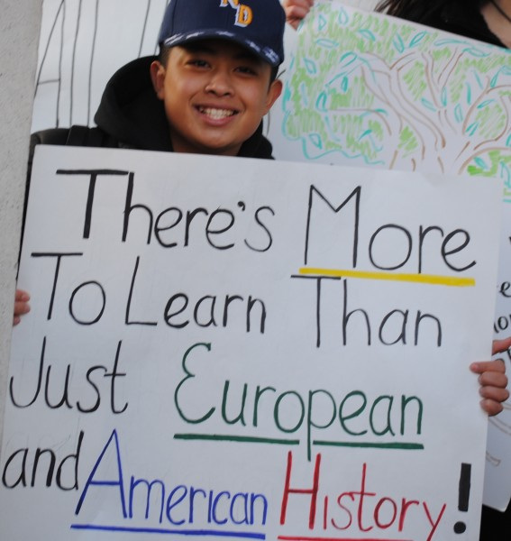 "A young man holds a hand-written sign reading: ""There's more to learn than just European and American History!"""