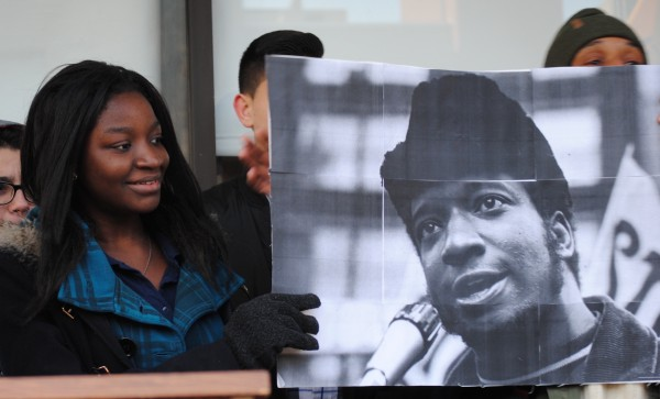 A female student of color holds a black-and-white image of a black man.