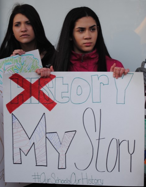 "Two young women holding a sign reading ""History"" and ""My Story"" with ""His"" crossed out with a red ""x""."