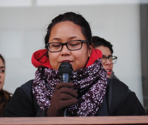 A young woman of color using a microphone speaks about ethnic studies at a Providence Student Union rally.