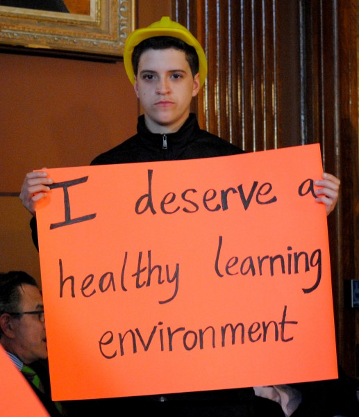 "A student wearing a yellow safety helmet holds up a large orange sign that says, ""I deserve a healthy learning environment""."
