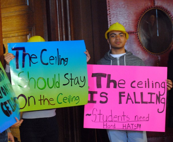 "Providence students wearing yellow hard hats hold signs, ""The ceiling should stay on the ceiling"" and ""the ceiling is falling"""