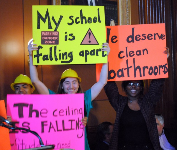 "Three Providence high schoolers lift colorful signs, ""My school is falling apart"", ""We deserve clean bathrooms"", and ""The ceiling is falling""."