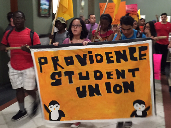 PSU Students march through Providence City Hall, carrying orange Providence Student Union banner.