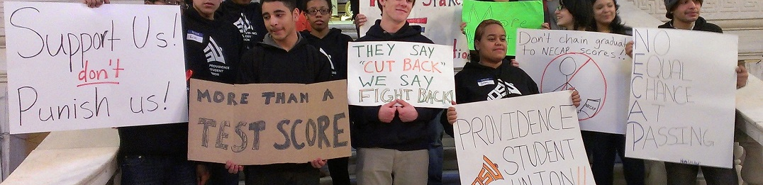 """PSU students holding signs reading """"More Than a Test Score,"""" """"Support Us, Don't Punish Us!"""" etc."""