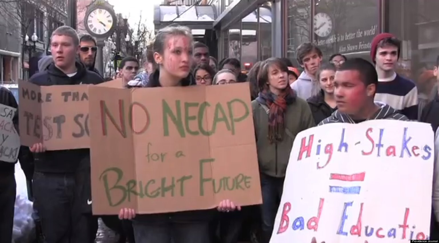 """Students holding hand-made signs, reading """"No NECAP for a bright future"""" and """"High Stakes = Bad Education"""""""