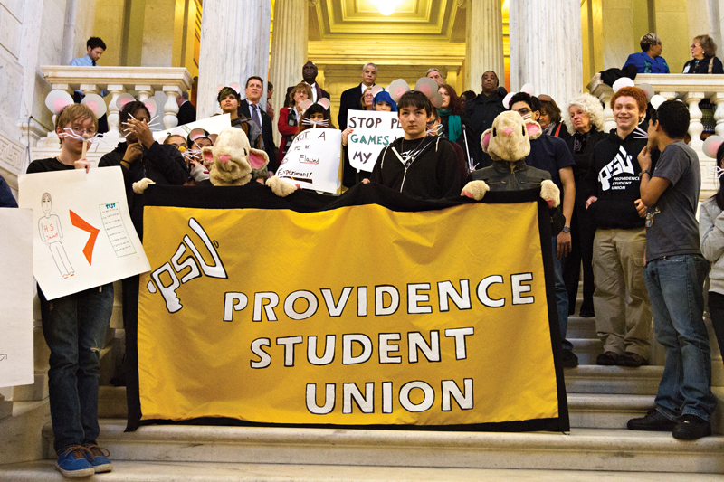 PSU students standing on interior State House steps holding orange Providence Student Union banner.