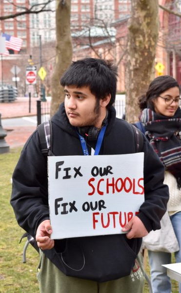 "A male student of color holds a sign, ""Fix our schools, Fix our future""."