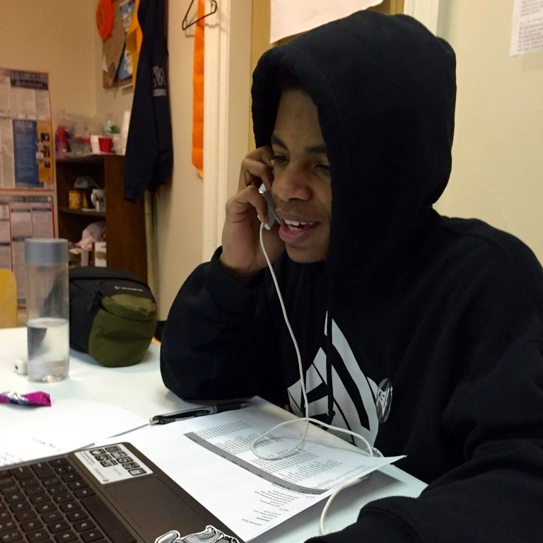 A young black student sits at a desk on the phone. He is wearing a black hoodie with the words 'PSU' written over it.