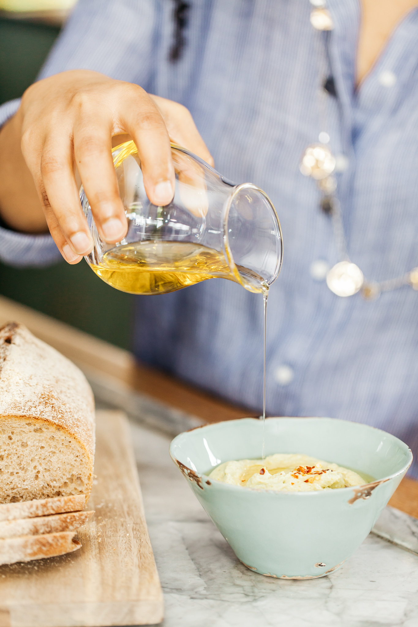 Oil being added to a hummus style dip.Food lifestyle photography for Bare Biology by Emma Gutteridge