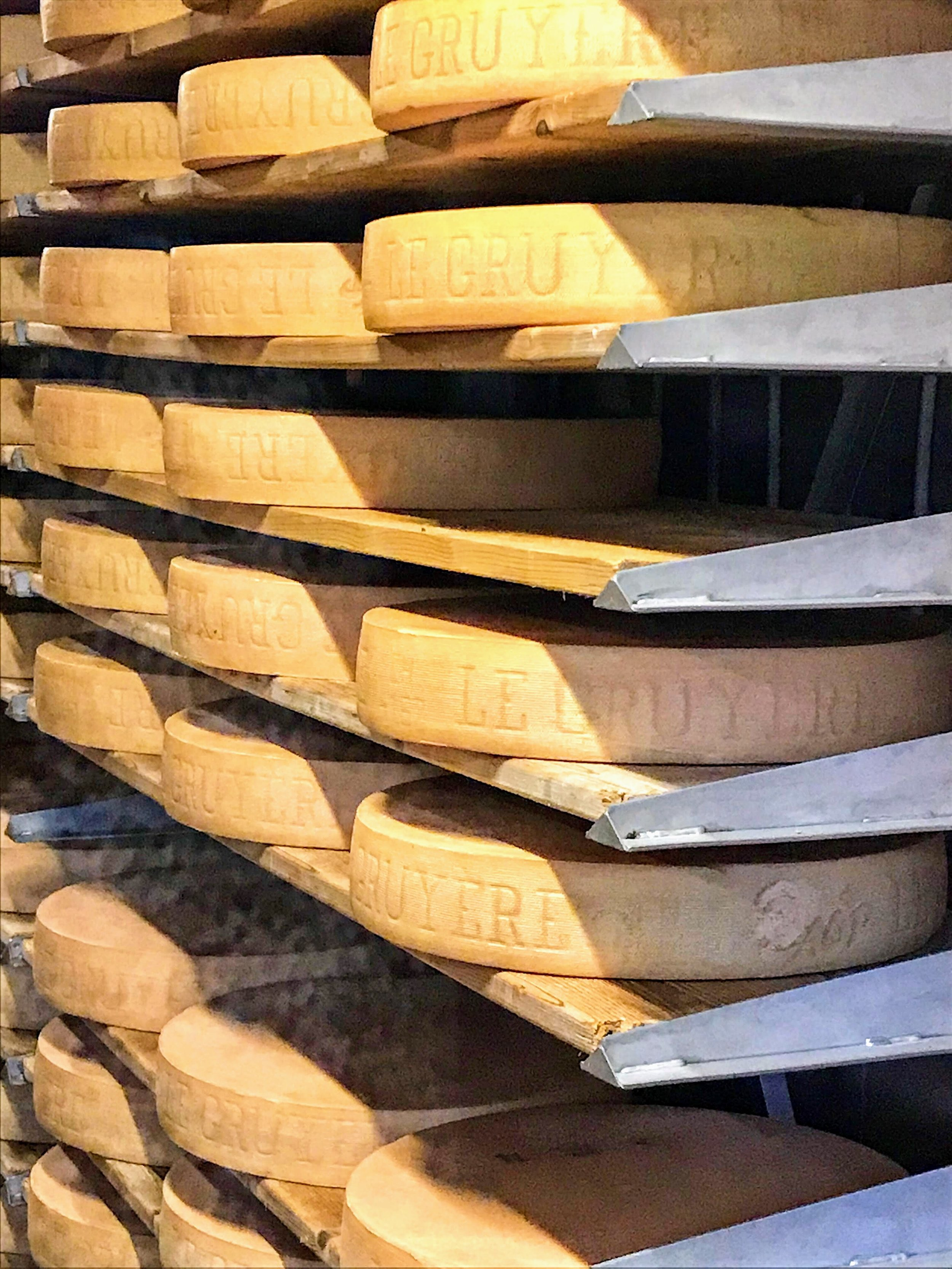 Wheels of gruyere cheese aging up to 24 months; gruyere cheesemakers in photos below