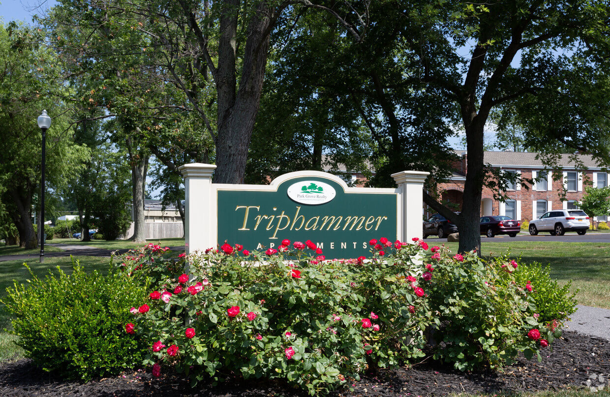 Close up view of Triphammer Apartments welcome sign in front garden