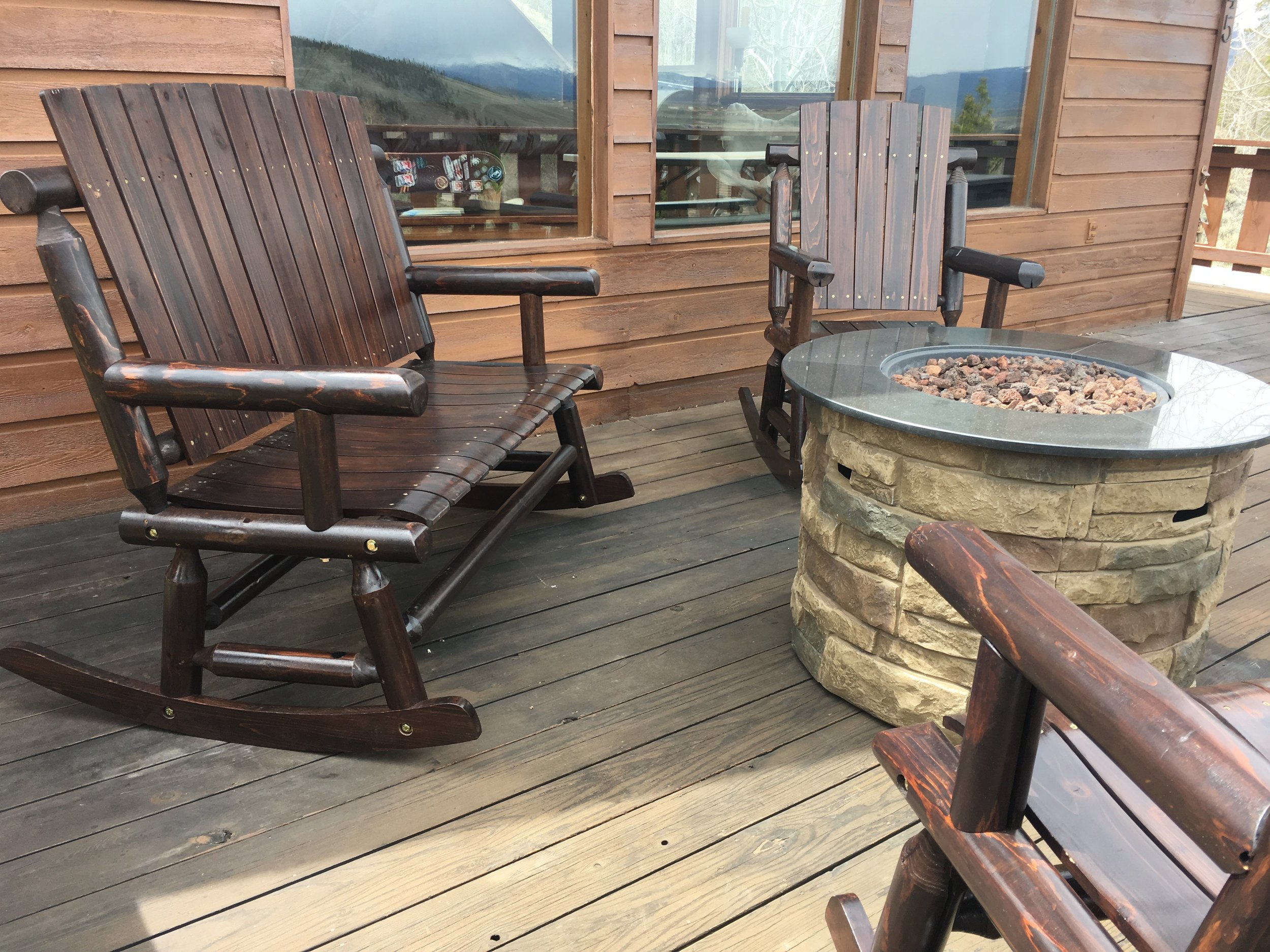 Deck with fire table and log furniture and picnic table