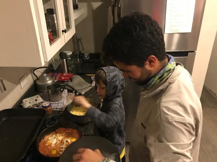 Josiah helps stir the shakshuka.