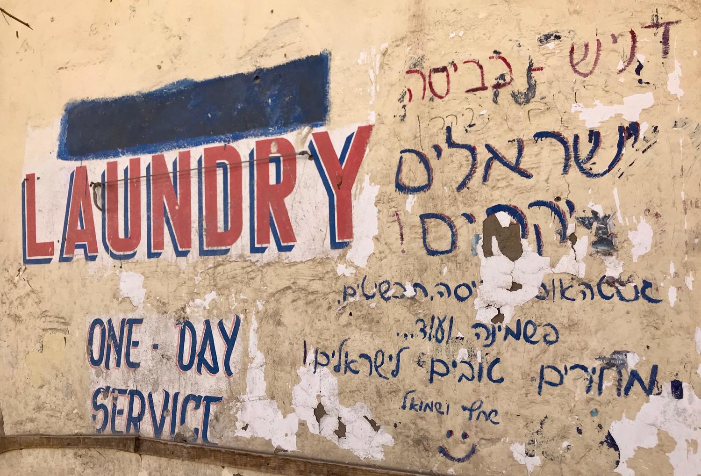 Hebrew graffiti in Leh, India advertises a local laundry service popular with Israeli trekkers.