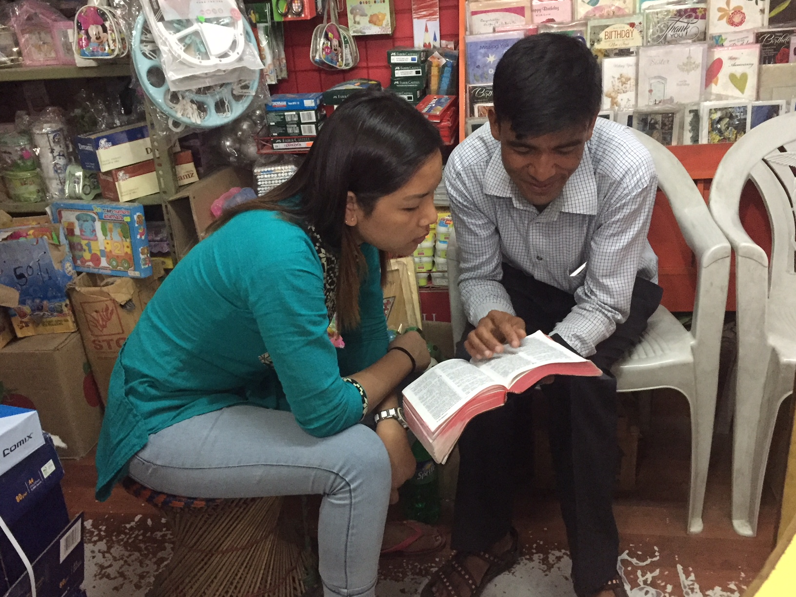 One of the brothers from Bishnu's house church shares from the Bible with the aforementioned young woman.