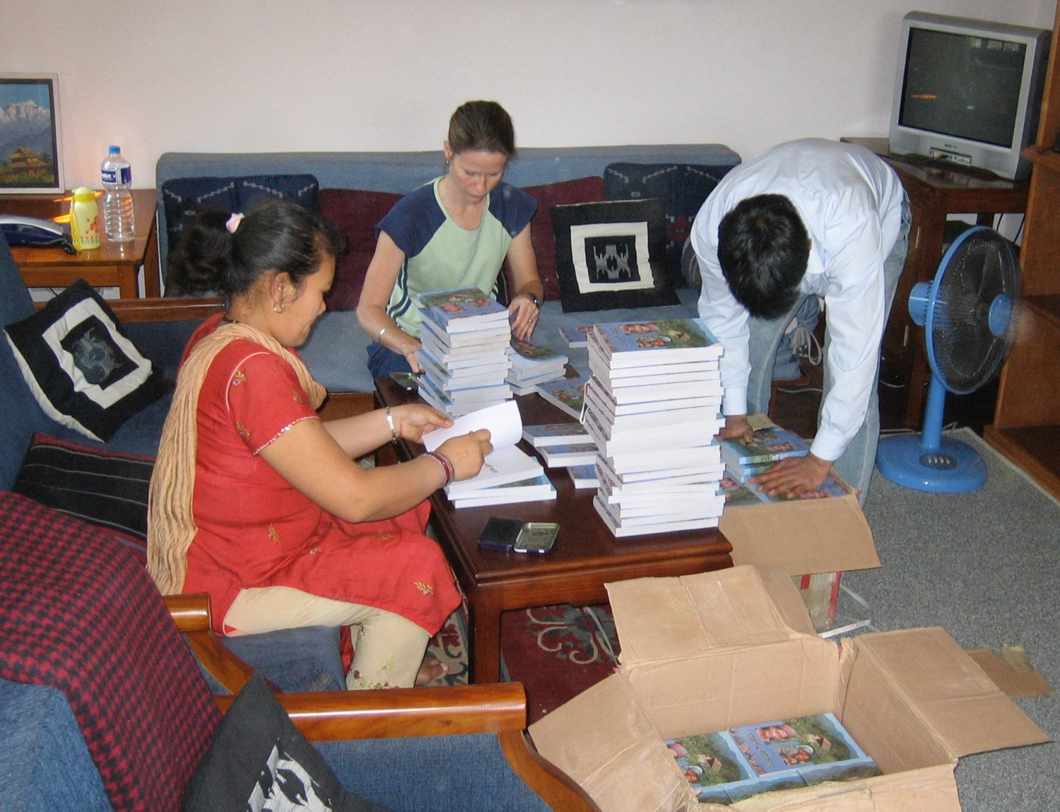 Brother Bishnu, sister Bimu, and Jamie stamp Nepali Bibles prior to a trip up into the mountains not long after we all first met (2007).