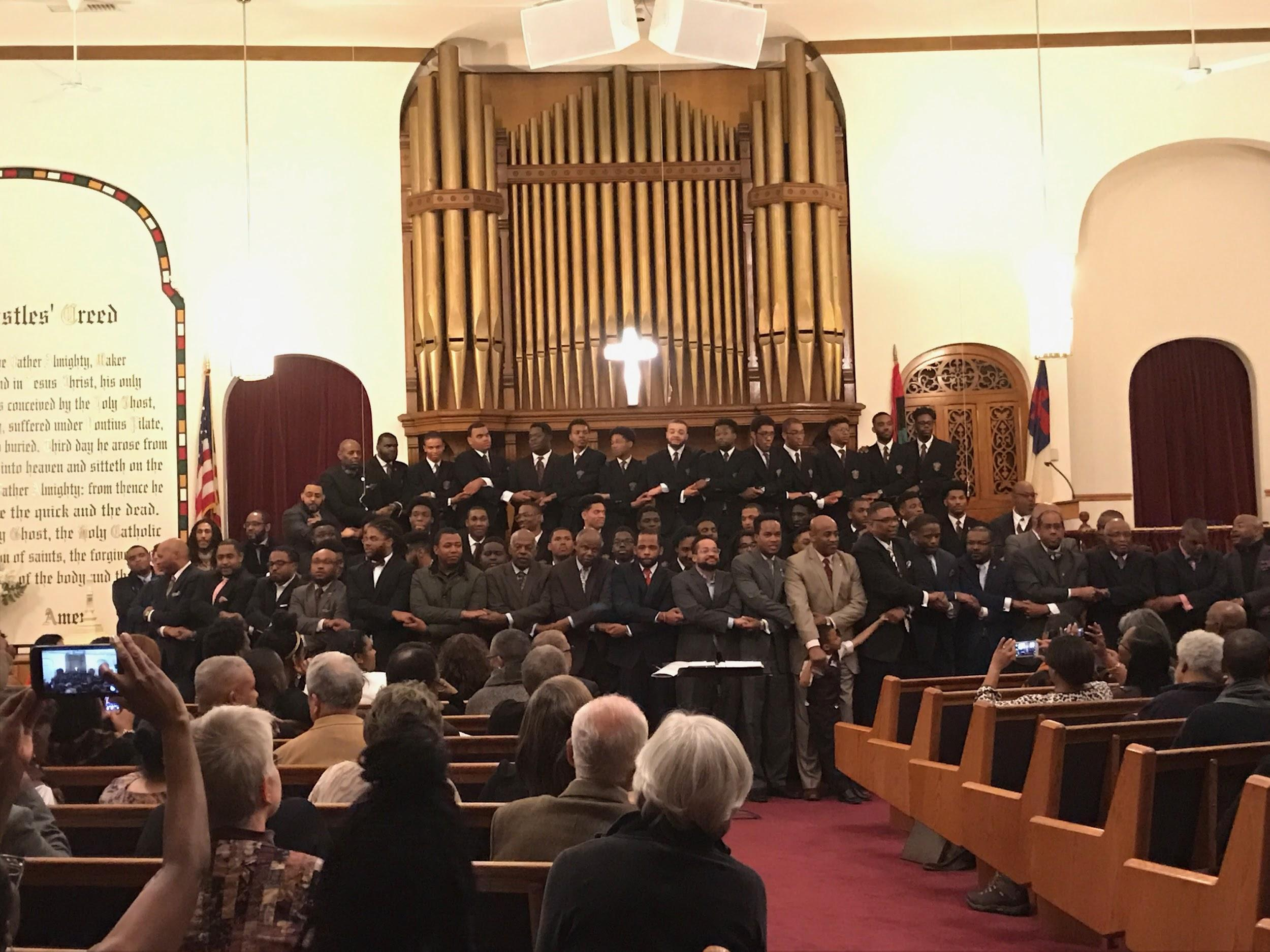 The Morehouse Glee Club and Morehouse Alumni holding hands and singing together.