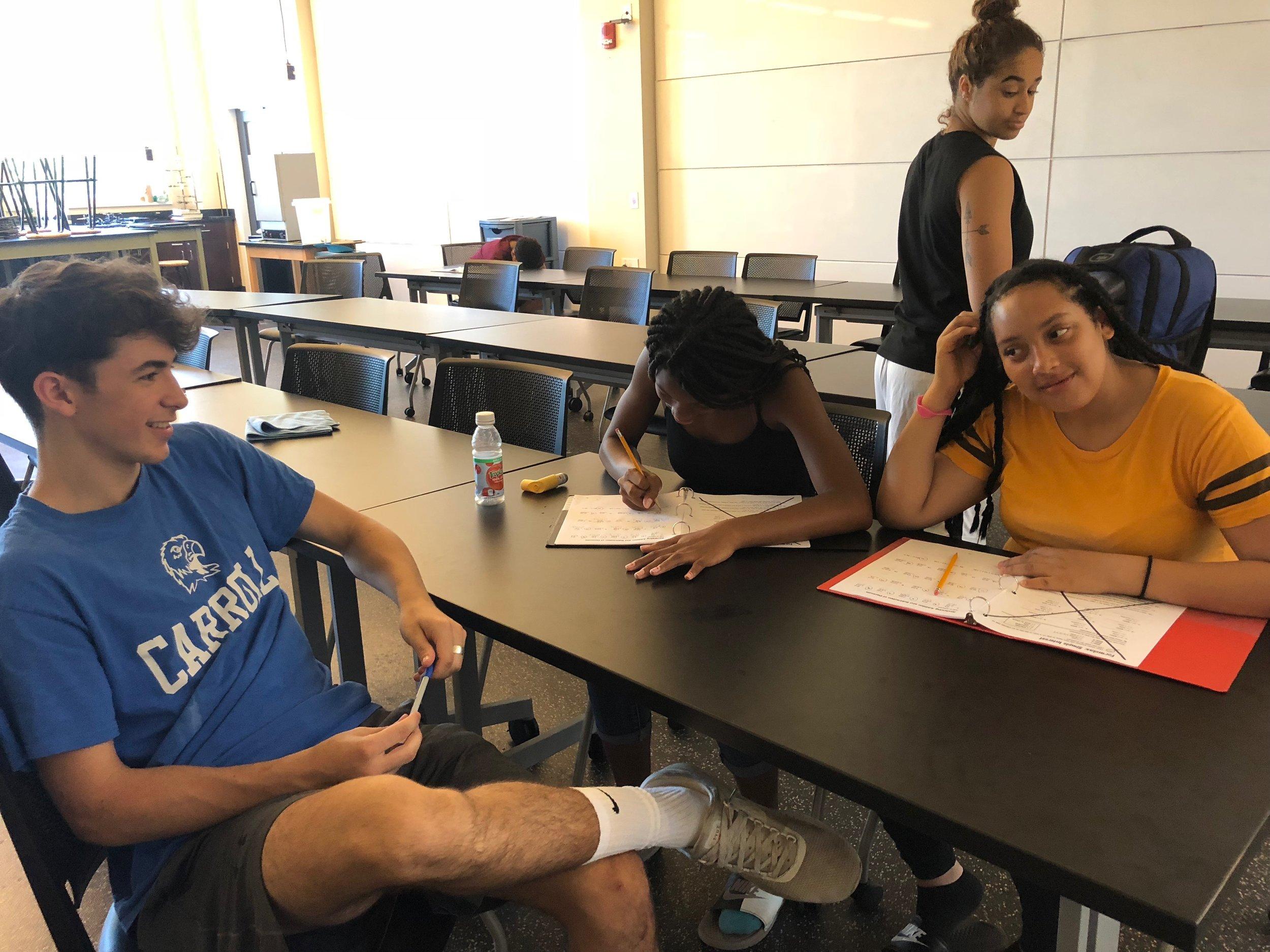 Counselor helping Nijah and Naomi with their math homework