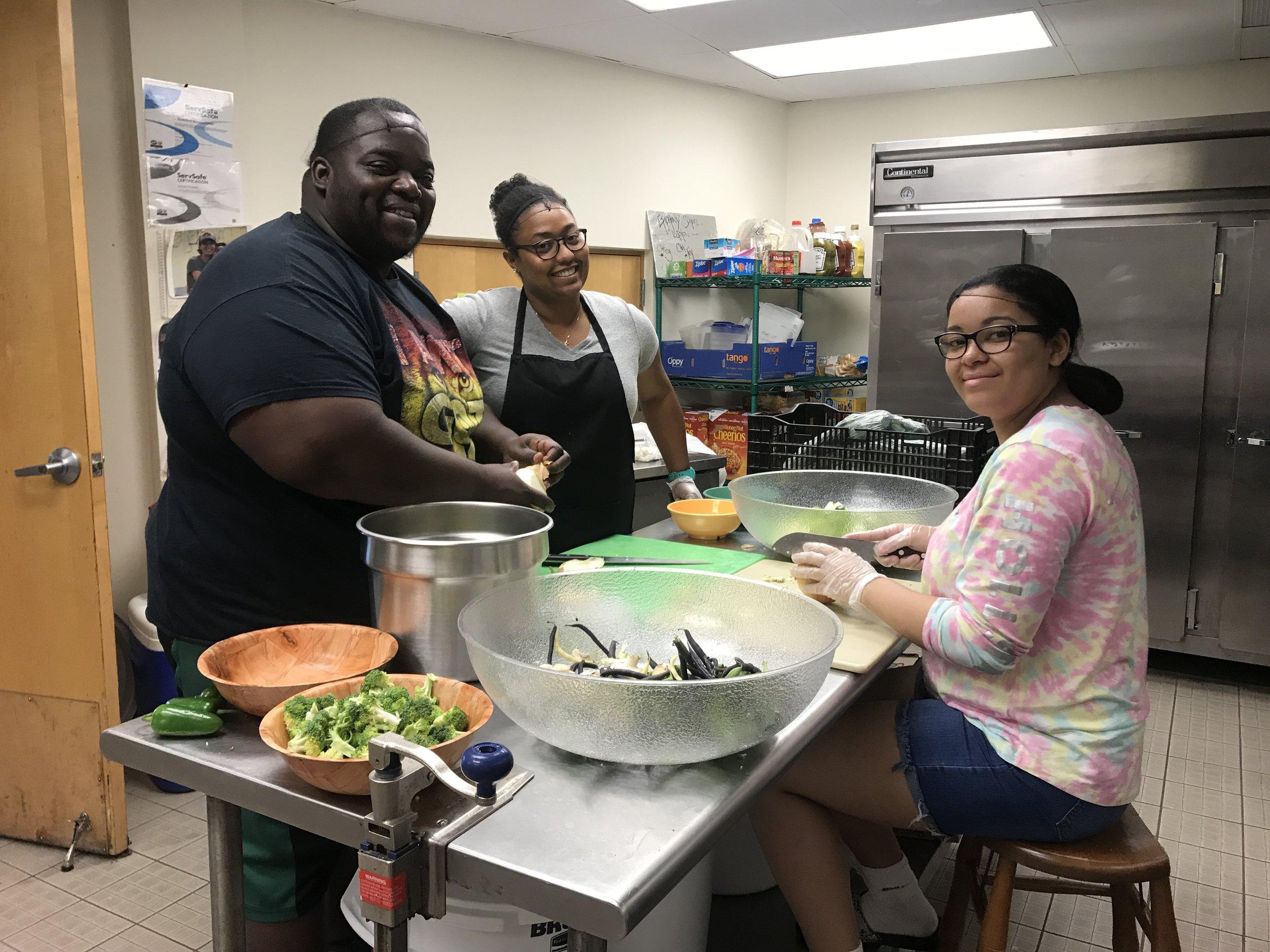 Chef Tey, Sabrina '08 and Jorelys '17 preparing the ingredients.