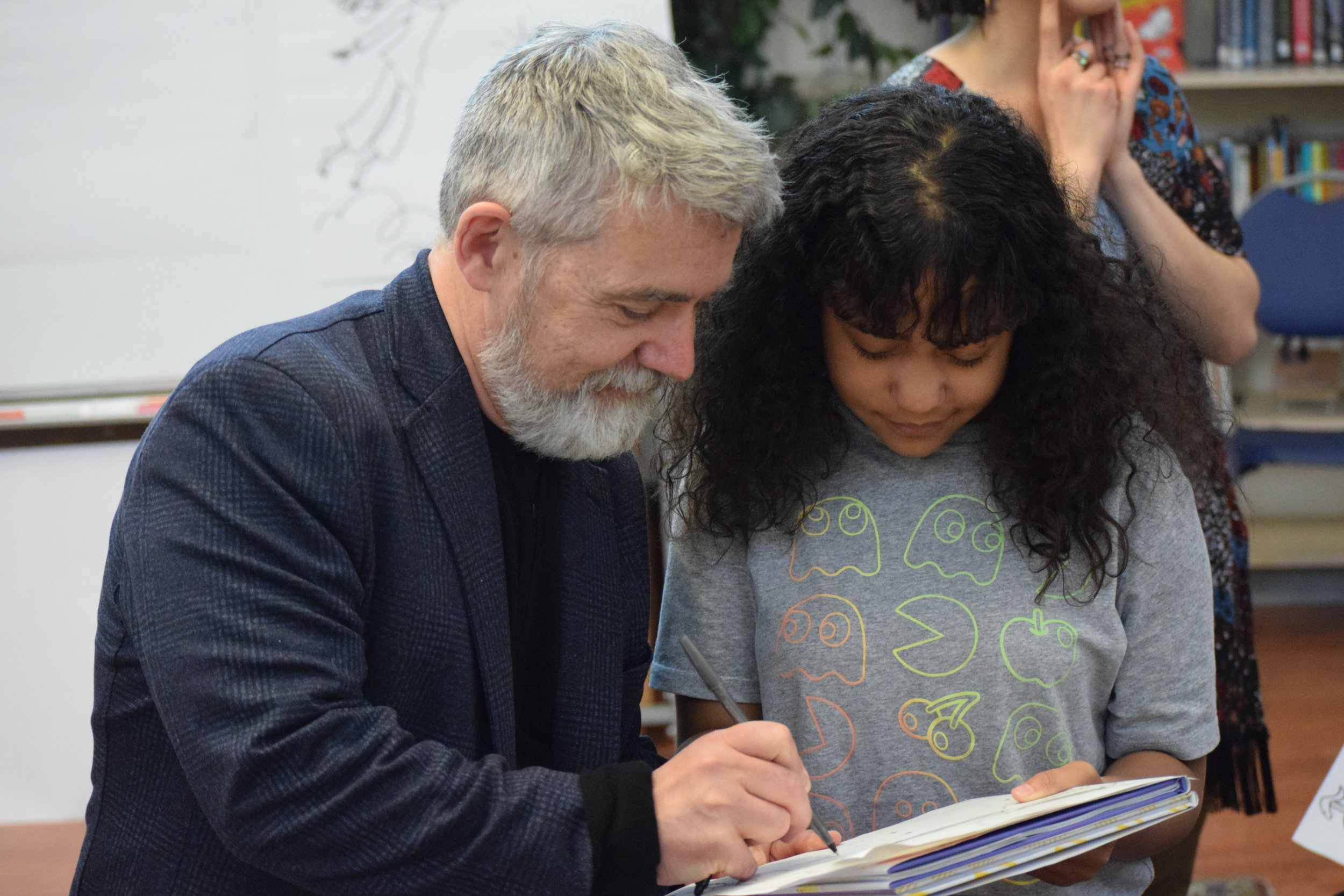 Peter Reynolds signing Andrialys's notebook.