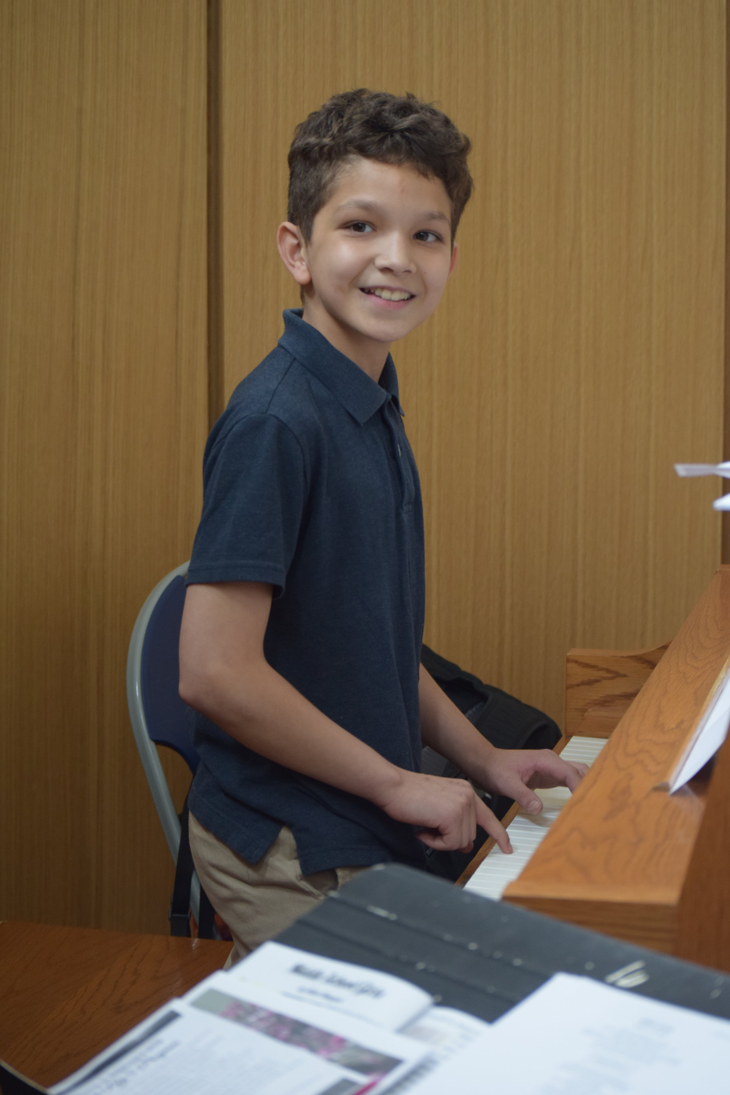 Steven playing the piano for the school.