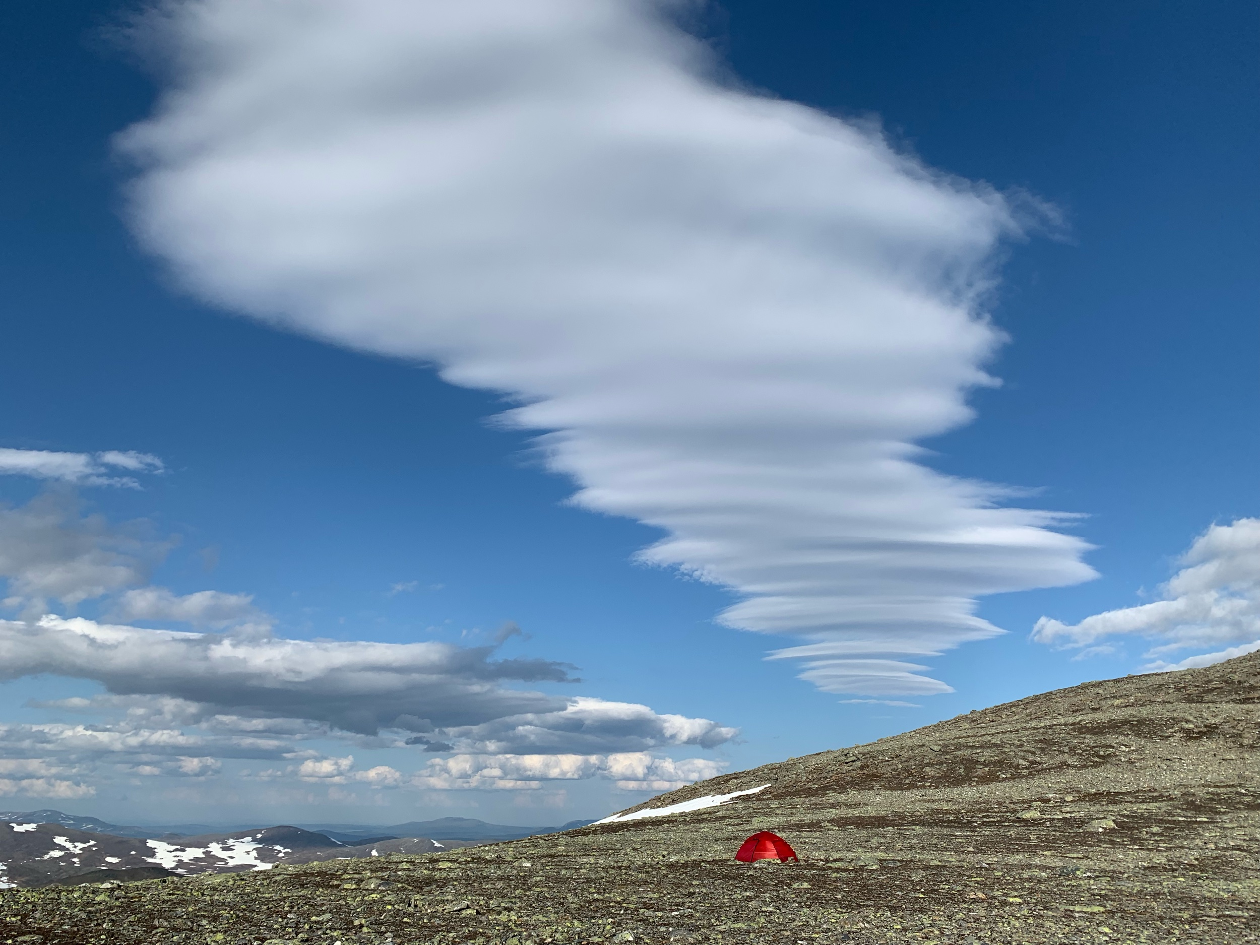 Lenticular clouds shaped by the wind above the tent.