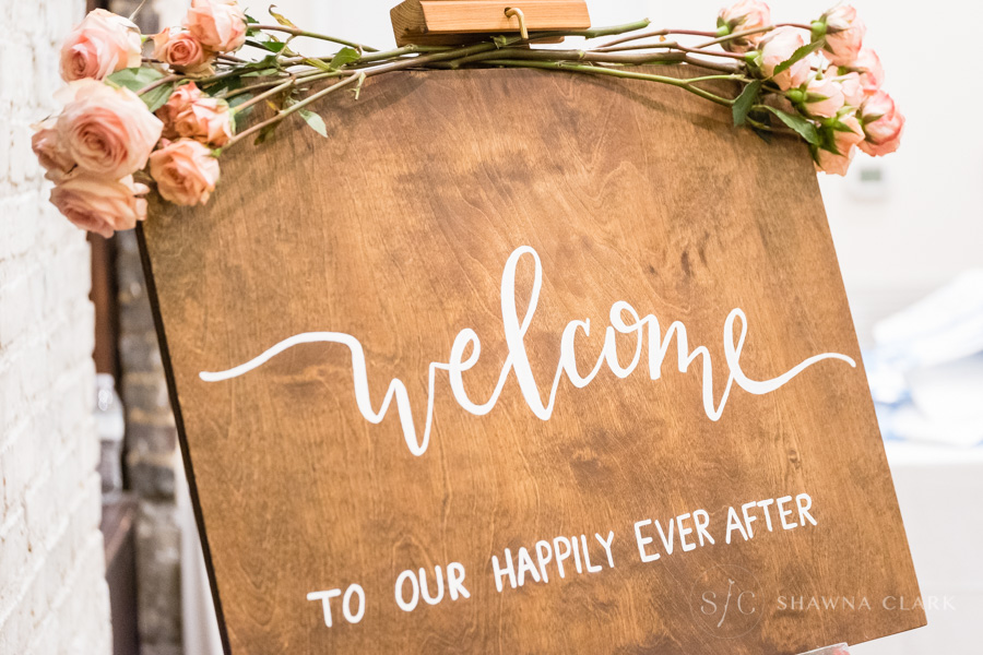 The Welcome Sign - Welcome signs are great. The layout of this pine wood sign is one of our favorites because it's elegant and simple. For the event, we displayed the large sign on a wooden art easel and attached soft pink spray roses using floral wire wrapped around the top of the easel. Best of all it's versatile. After the wedding, this sign can be hung in your entryway or over the mantel to welcome each person that enters your home to your happily ever after.
