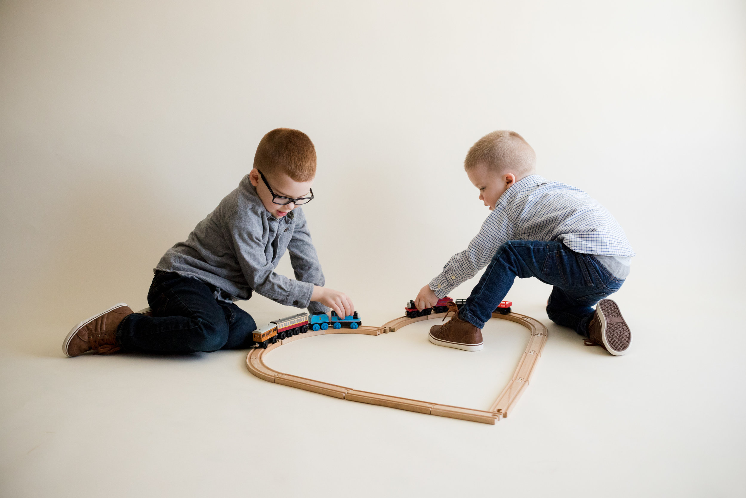 Two boy children playing with toy trains during indoor photo session in Cedar Rapids, Iowa.