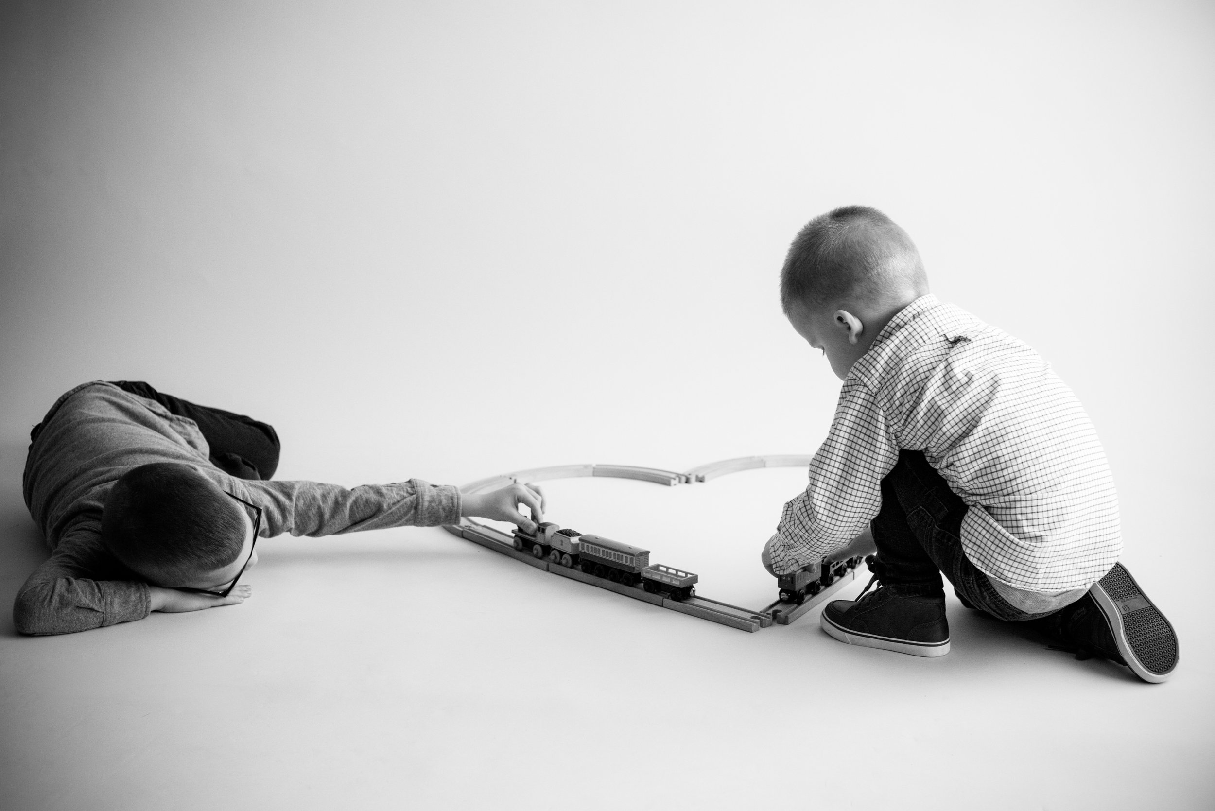 Two boy children playing with toy trains during photo session in Cedar Rapids, Iowa in black and white.