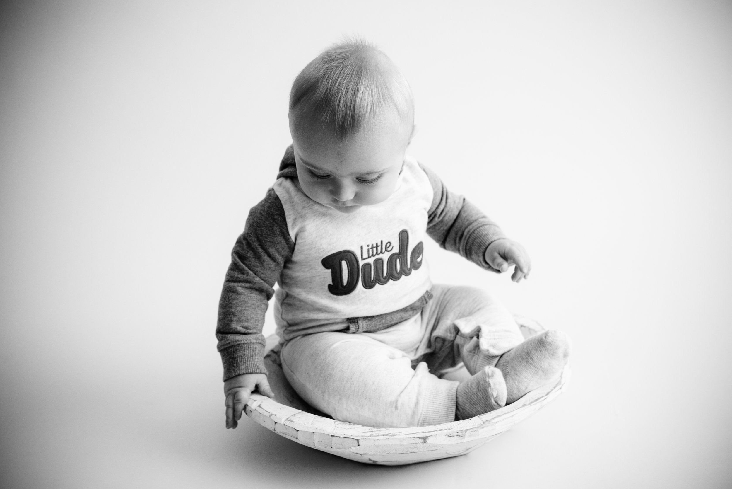 Black and white photo of a six month old baby boy sitting up on own in a bowl in Iowa.
