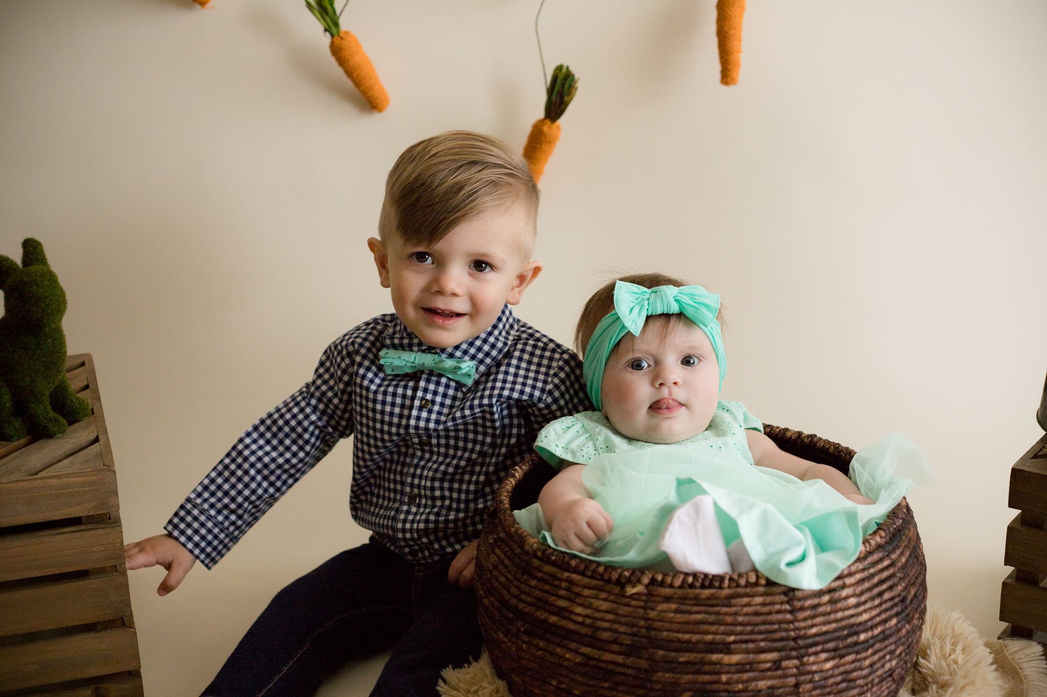 Boy and baby girl children sitting for Easter Mini Session photo in Cedar Rapids, Iowa.